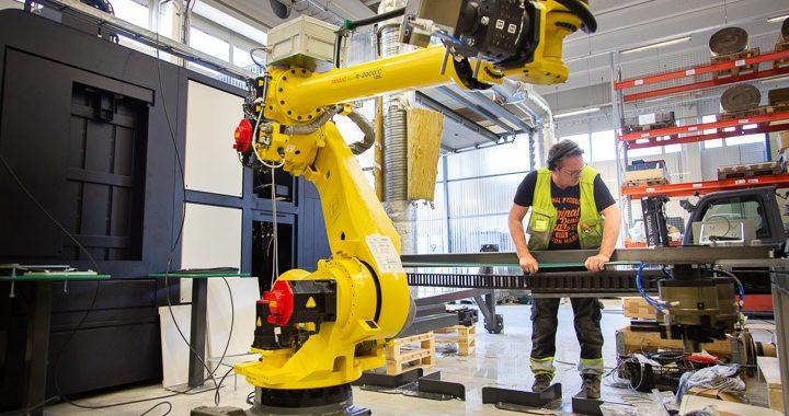 Mies asentaa robottisolua tehtaassa